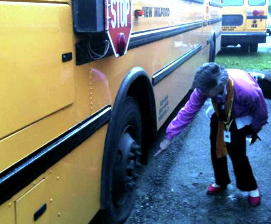 SPECTRUM/New Milford bus driver Mary Boland points to one of the estimated 93 tires slashed some time late Sunday or early Monday, June 13, 2011 at the All-Star Tranportation bus depot on Dodd Road. Photo: Nanci Hutson, Carol Kaliff / The News-Times