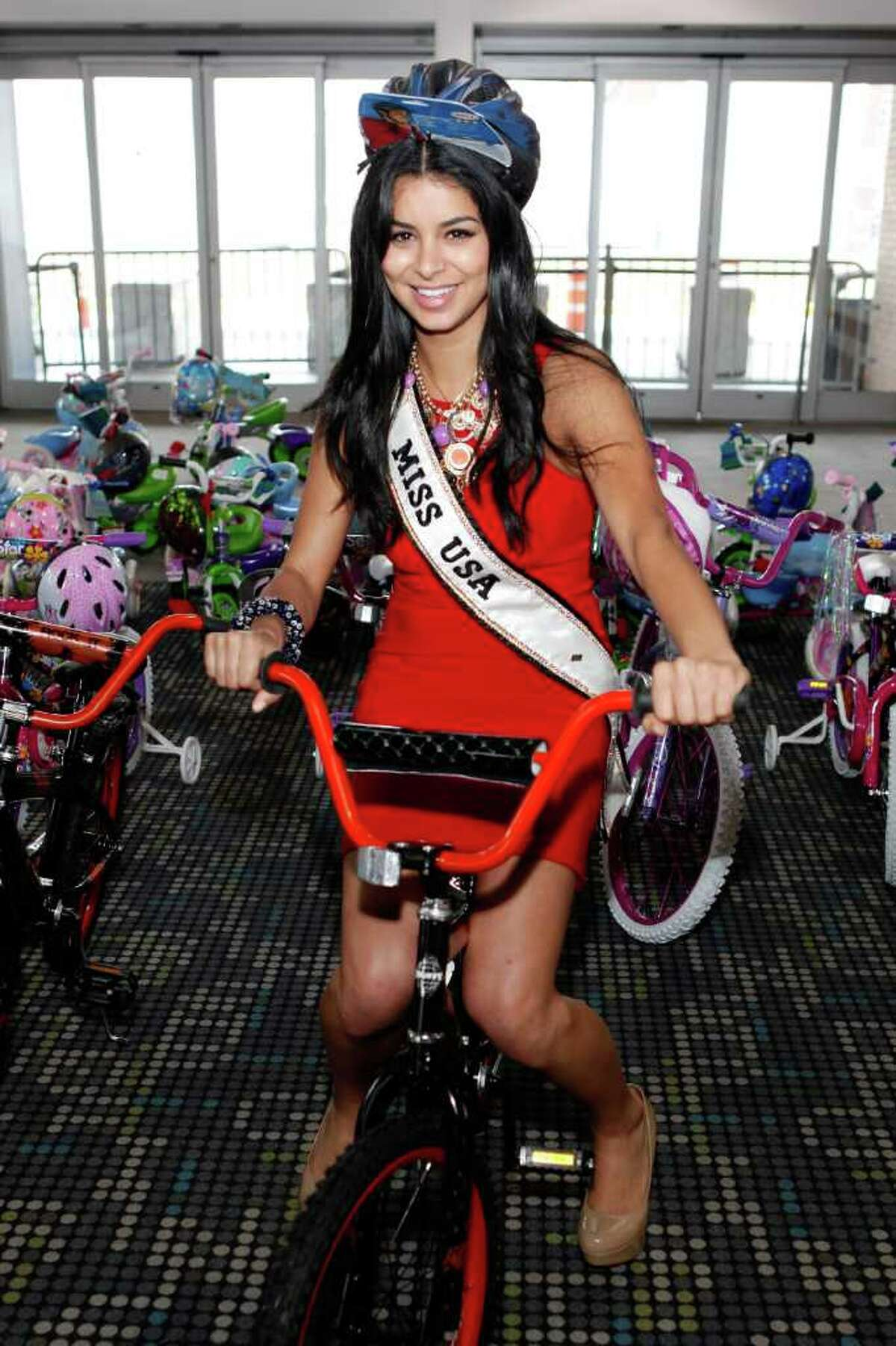 Miss USA Rima Fakih builds bikes for children at Pier 88 on May 26, 2011 in New York City.