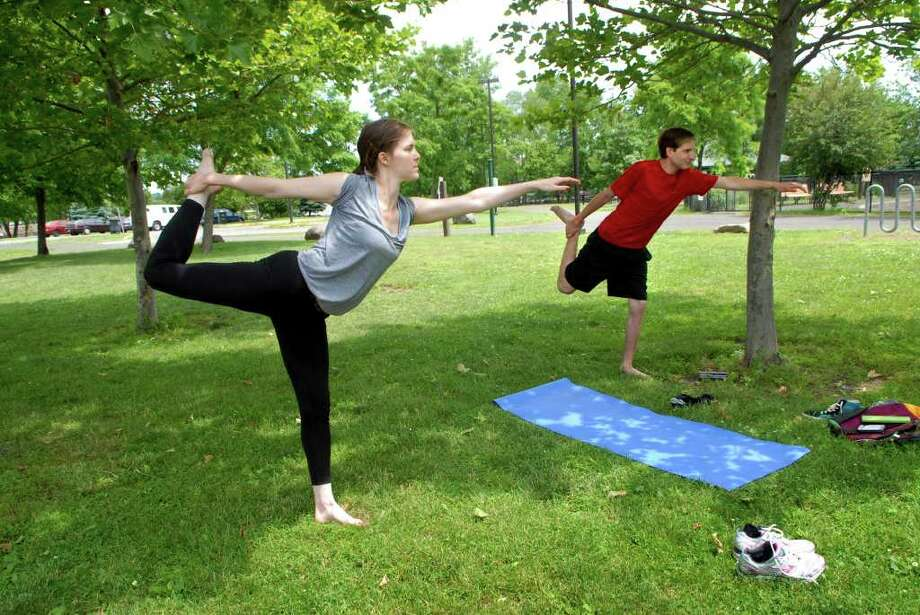 Julie Michael and D. J. Weiss do yoga in Kosciuszko Park in Stamford, Conn. on Monday June 13, 2011, their day off from their jobs at the Big Apple Circus. Michael is a wardrobe supervisor and Weiss works on the ring crew and is also a clown but isn't performing in this show. Photo: Dru Nadler / Stamford Advocate Freelance