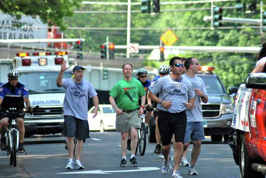 Special Olympian Stephen Caird (center) of New Canaan ran through Darien alongside Darien and New Canaan police officers as part of the Connecticut Law Enforcement and Special Olympics Torch Run last Friday, June 10. Photo: Jeanna Petersen Shepard / Darien News