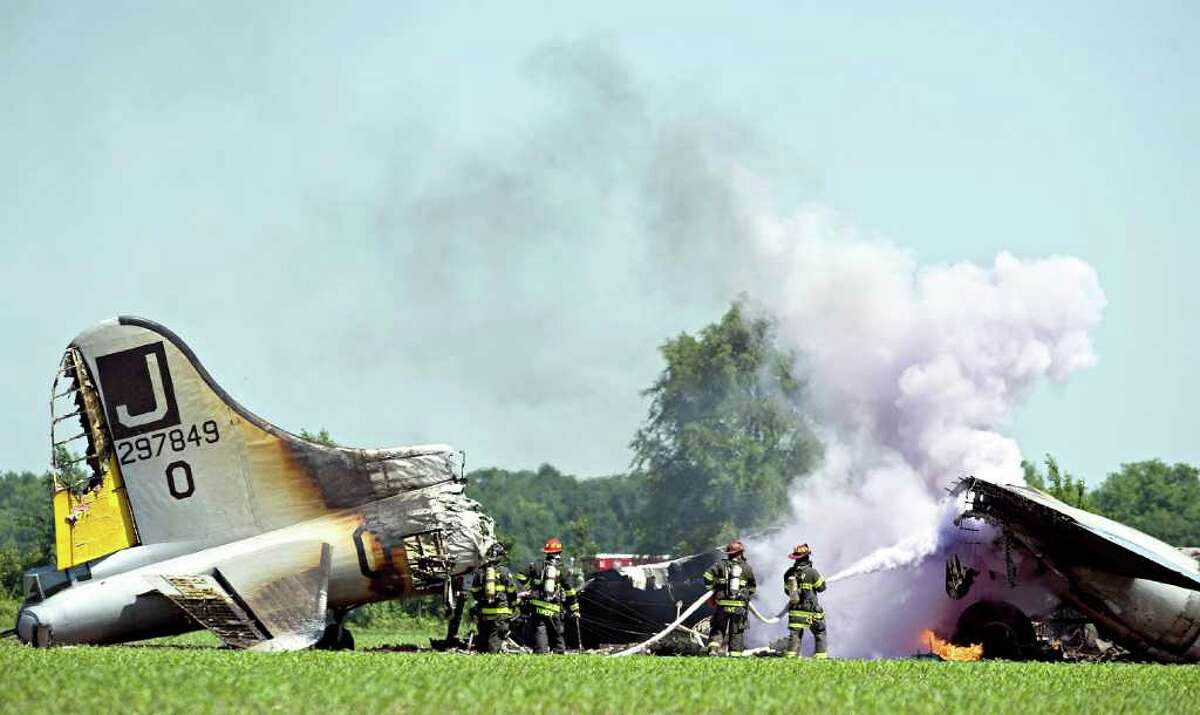 Oswego Fire Protection District and other area fire departments extinguish flames in the wreckage of a World War II-era B-17 bomber after it burned following an emergency landing in a farm field in Oswego, Ill., Monday, June 13, 2011. The vintage plane had taken off from nearby Aurora Municipal Airport. The Federal Aviation Administration believes the seven people on board the plane escaped uninjured.