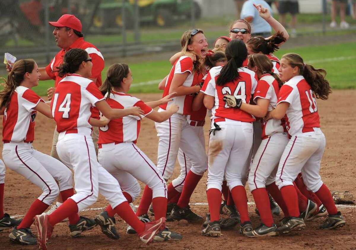 Foran players charge the mound in celebration after defeating Bacon Academy 3-0 in the Class L state softball championships at West Haven High School on Monday, June 13, 2011.