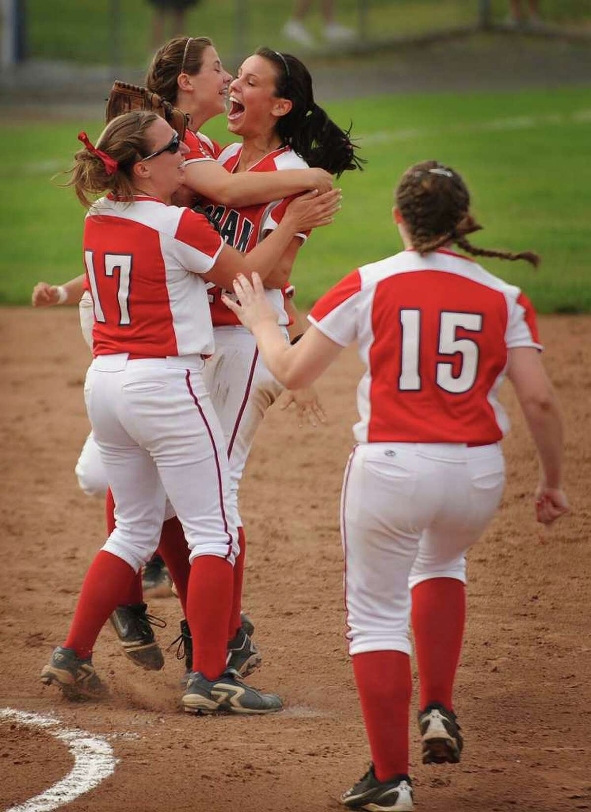 Foran players charge the mound in celebration after defeating Bacon Academy 3-0 in the Class L state softball championships at West Haven High School on Monday, June 13, 2011. Winning pitcher Taylor Harkness, left, was named tournament MVP.