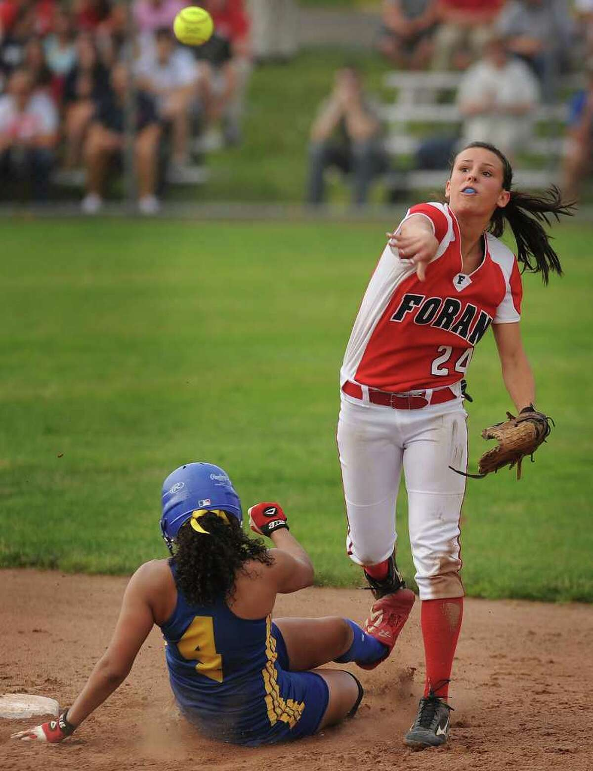 Foran shortstop Brooke Phelan turns an inning ending double play over Bacon Academy's Makaila Kowalsky in the sixth inning of the Lions' 3-0 victory in the Class L state softball championships at West Haven High School on Monday, June 13, 2011.