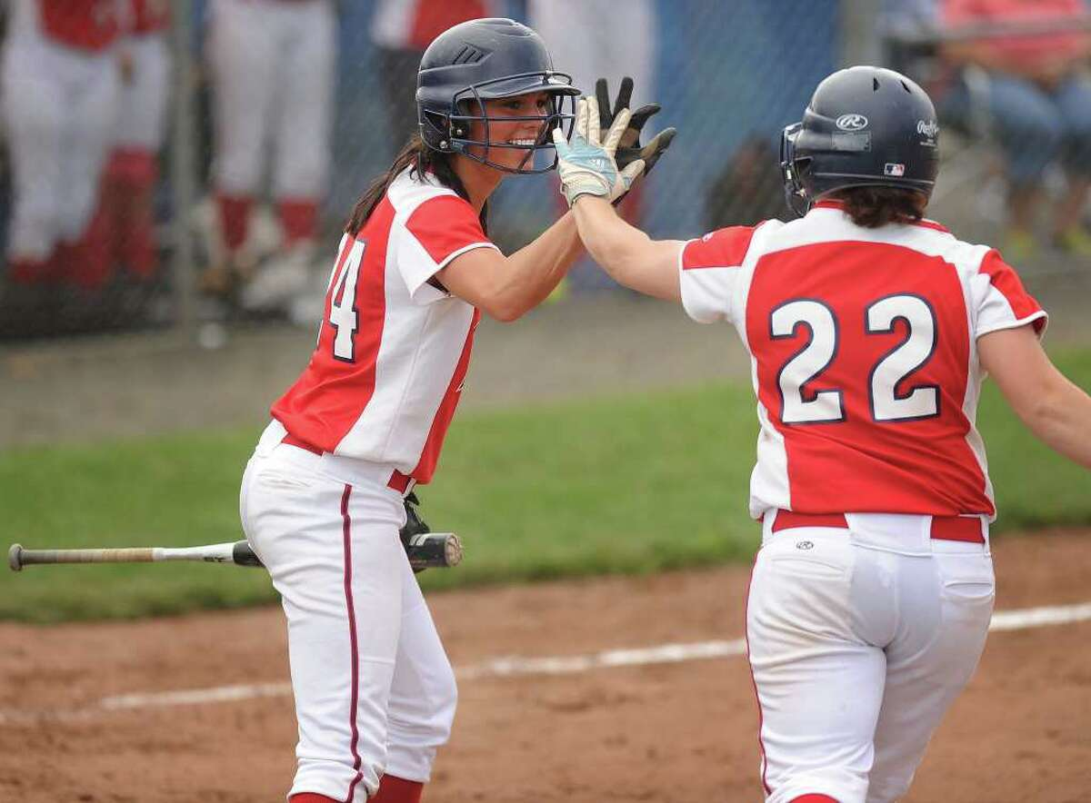 Foran's Brooke Phelan, left, high fives teammate Rachel Booth after Booth drove Phelan in with the first run of the game in the opening inning of the Class L state championship softball game at West Haven High School on Monday, June 13, 2011. Foran of Milford defeated Bacon Academy 3-0.