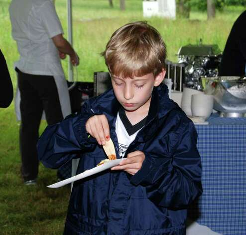 Eight-year-old Jay Knight concentrates on the 60 Hour Short Ribs prepared by Chef Michel Richard of Washington, D.C. Photo: Jeanna Petersen Shepard / New Canaan News