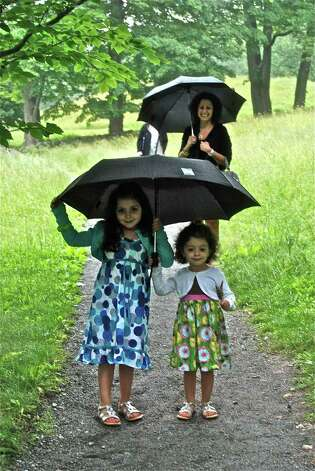 A little dark, but dry, under the umbrella!  Six-year-old Isabella Celano and her little sister Lianna make there way from the Painting Gallery back to the tent, with their mother Rosalba Celano trailing behind them. Photo: Jeanna Petersen Shepard / New Canaan News