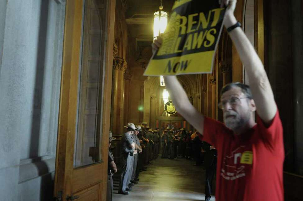 New York State Troopers stand in a line outside of Governor Andrew Cuomo's capitol offices as New York City tenants and tenant advocates hold a rally inside the capitol on Monday afternoon, June 13, 2011 in Albany. The group was calling on lawmakers to pass a bill with stronger rent laws and not just extend the existing rent control law. (Paul Buckowski / Times Union)
