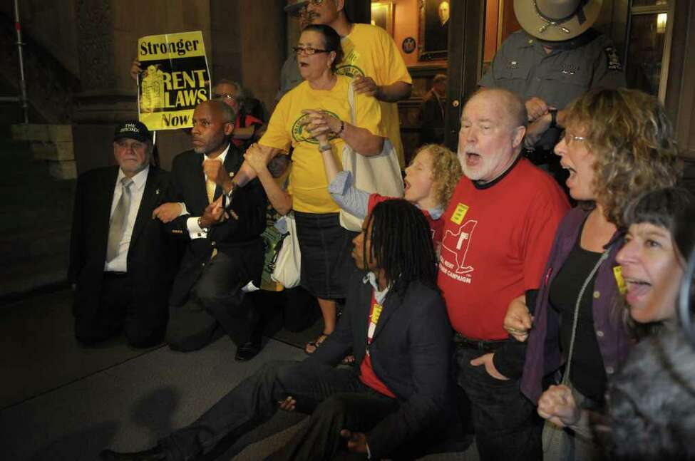 State Assemblyman Jose Rivera, far left, State Senator Bill Perkins, second from left, join with New York City tenants and tenant advocates as they sit down in front of the doors to Goveror Andrew Cuomo's offices during a rally inside the capitol on Monday afternoon, June 13, 2011 in Albany. The group was calling on lawmakers to pass a bill with stronger rent laws and not just extend the existing rent control law. State Police arrested several of the protestors who would not move away from the doors. (Paul Buckowski / Times Union)