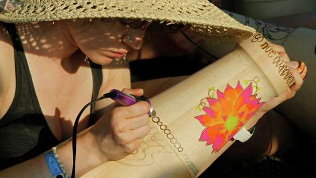Kristal Schuck of Pennsylvania constructs a drum during the Bonnaroo Music and Arts Festival in Manchester, Tenn., Sunday, June 12, 2011. Photo: AP