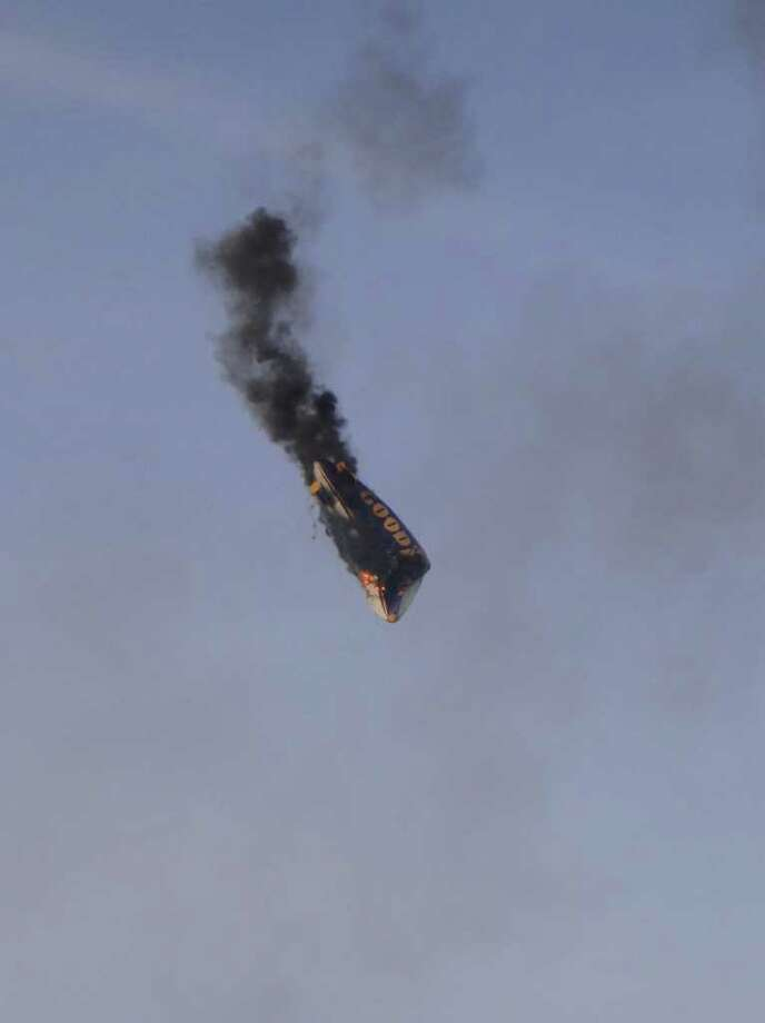 A Goodyear blimp crashes near Oberursel, western Germany, on Sunday. The pilot of the blimp was killed and three passengers had to leap to safety when the aircraft caught fire and crashed, a police spokesman said. The blimp had been making a promotional flight to mark a local festival. Photo: AFP, AFP/Getty Images / 2011 ImageForum