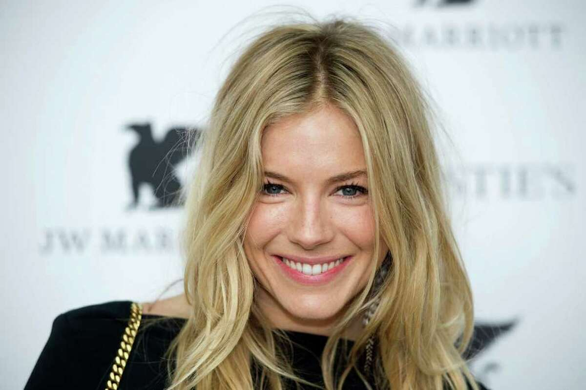 British actress Sienna Miller poses for photographers as she arrives to host a private viewing reception for the forthcoming sale of 'The Beatles Illuminated: The Discovered Works of Mike Mitchell' in central London.