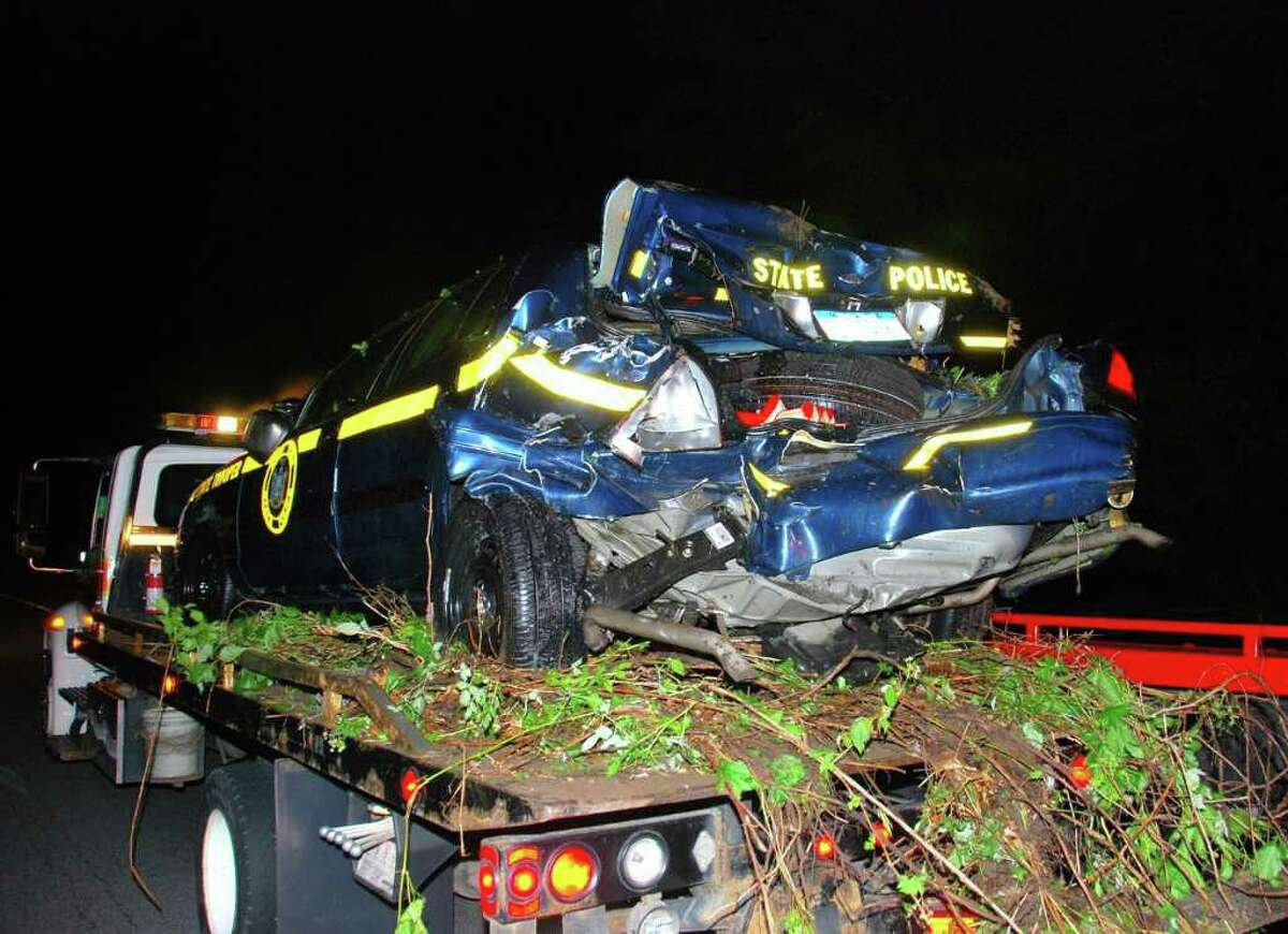 State Police said a 39-year-old trooper is fortunate he suffered only a concussion when his patrol car was rear-ended Monday evening by an SUV towing a U-Haul on the Northway. The police vehicle flipped onto its roof and both drivers were taken to the hospital. (Tom Heffernan / Special to the Times Union)