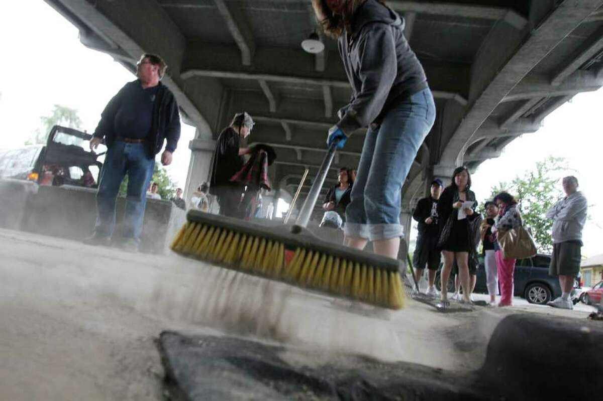 Barbara Luecke sweeps the concrete in front of Fremont's iconic Troll during a community cleanup on Tuesday.