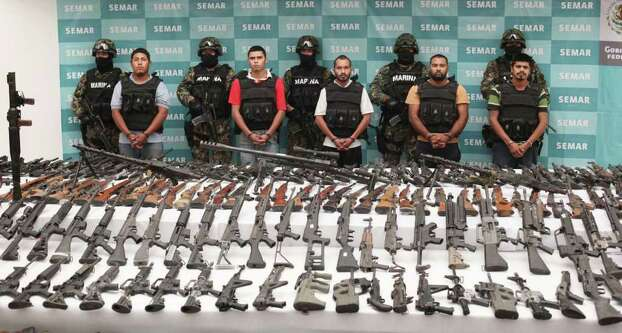 Soldiers escort five alleged members of the Zetas drug gang during their presentation to the press in Mexico City, Thursday, June 9, 2011. Over 200 weapons have been seized after arresting the five men at a Navy check-point yesterday, near the city of Villa Union, in Mexico's Coahuila state. Photo: AP