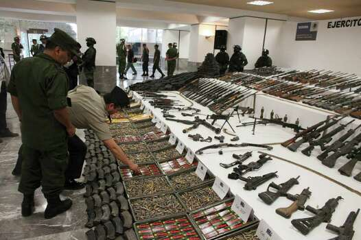 "Soldiers review a weapons cache that includes 154 rifles and shotguns and over 92,000 rounds of ammunition during a media presentation, in Mexico City, Friday June 3, 2011. Army Gen. Edgar Luis Villegas said Friday the weapons were found in ""a subterranean stockpile"" at a ranch near the northern city of Monclova this week.  Authorities believe the weapons belonged to the Zetas drug cartel. Photo: AP"