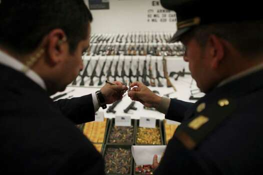 "Mexican army officers inspect seized ammunition during a media presentation of a weapons cache that includes 154 rifles and shotguns and over 92,000 rounds of ammunition, in Mexico City, Friday June 3, 2011. Army Gen. Edgar Luis Villegas said Friday the weapons were found in ""a subterranean stockpile"" at a ranch near the northern city of Monclova this week.  Authorities believe the weapons belonged to the Zetas drug cartel. Photo: AP"