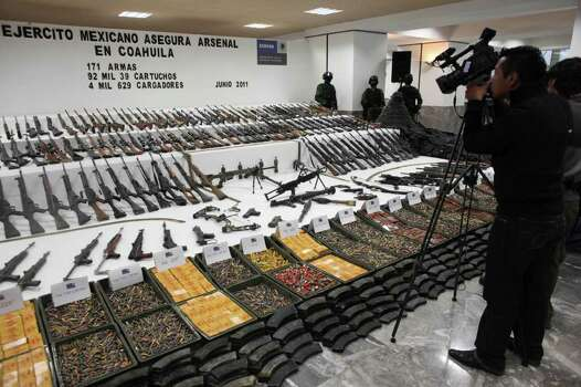 "Soldiers stand guard during a media presentation as a camerman films a weapons cache that includes 154 rifles and shotguns and over 92,000 rounds of ammunition, in Mexico City, Friday June 3, 2011. Army Gen. Edgar Luis Villegas said Friday the weapons were found in ""a subterranean stockpile"" at a ranch near the northern city of Monclova this week.  Authorities believe the weapons belonged to the Zetas drug cartel. Photo: AP"