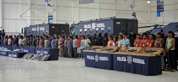 Federal police present to the news media a cache of weapons and nearly 50 suspects of two major drug cartels in Mexico City, Saturday May 28, 2011. The suspects include 36 members of the La Familia cartel and 10 members of the Zetas drug gang. Police said the alleged La Familia gang members were detained in connection with the attack on a federal police helicopter Tuesday that wounded two officers and forced the craft to land. Authorities added that the 10 Zeta members were detained Friday at a ranch in Cancun, where a kidnapping victim was found and released. Photo: AP