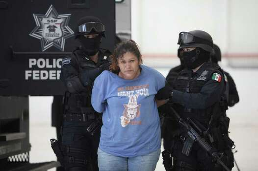 Federal police escort one of nearly 50 suspects of two major drug cartels to her presentation to the news media in Mexico City, Saturday May 28, 2011. The suspects include 36 members of the La Familia cartel and 10 members of the Zetas drug gang. Police said the alleged La Familia gang members were detained in connection with the attack on a federal police helicopter Tuesday that wounded two officers and forced the craft to land. Authorities added that the 10 Zeta members were detained Friday at a ranch in Cancun, where a kidnapping victim was found and released. Photo: AP