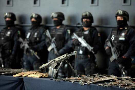 Federal police present to the news media a cache of weapons that were seized when they detained nearly 50 suspects of two major drug cartels in Mexico City, Saturday May 28, 2011. The suspects include 36 members of the La Familia cartel and 10 members of the Zetas drug gang. Police said the alleged La Familia gang members were detained in connection with the attack on a federal police helicopter Tuesday that wounded two officers and forced the craft to land. Authorities added that the 10 Zeta members were detained Friday at a ranch in Cancun, where a kidnapping victim was found and released. Photo: AP