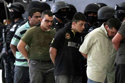 Federal police escort nearly 50 suspects of two major drug cartels to their presentation to the news media in Mexico City, Saturday May 28, 2011. The suspects include 36 members of the La Familia cartel and 10 members of the Zetas drug gang. Police said the alleged La Familia gang members were detained in connection with the attack on a federal police helicopter Tuesday that wounded two officers and forced the craft to land. Authorities added that the 10 Zeta members were detained Friday at a ranch in Cancun, where a kidnapping victim was found and released. Photo: AP