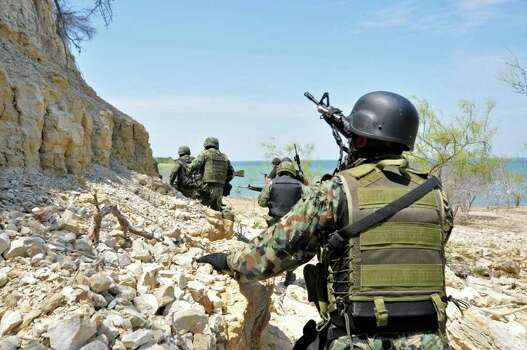 In this image released by the Mexican Navy on Monday, May 9, 2011, a group of Mexican Navy marines conduct an operation in an island on Falcon Lake in the northeastern state of Tamaulipas, Mexico, Sunday, May 8, 2011. One marine and 12 suspected gunmen of the Zetas drug cartel were killed when the marines discovered a camp, which is believed to have been used as a launching point for smuggling marijuana into Texas by speedboat. Photo: AP
