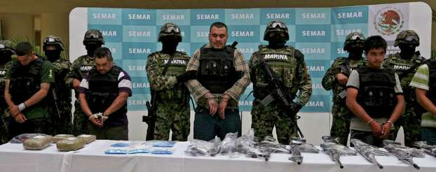"Navy members escort Martin Omar Estrada Luna, center, alias ""El Kilo,"" and alleged members of his gang in front of seized weapons and packages containing narcotics during a presentation to the press in Mexico City, Sunday, April 17, 2011. The Mexican Navy said Saturday it had captured Estrada Luna, the presumed leader of the San Fernando cell of the Zetas drug gang, suspected in the case of the mass graves found in Tamaulipas, as well as the migrant massacre last August in the violent border state across from Texas. Photo: AP"