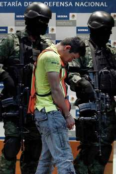 "Soldiers escort Julian Zapata Espinosa, aka ""El Piolin"" alleged member of the Los Zetas drug cartel and main suspect in the killing of U.S. Immigration and Customs, ICE, agent Jaime Zapata, during a presentation for the media in Mexico City, Wednesday, Feb. 23, 2011. Zapata and fellow agent Victor Avila, were attacked Feb. 15 when traveling along a highway in Mexico's San Luis Potosi state. Avila survived the attack. Photo: AP"
