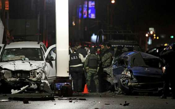 Soldiers, state police and forensic investigators work at a crime scene after a shootout between soldiers and alleged cartel gunmen on the outskirts of Monterrey, Mexico, Saturday, Feb. 12, 2011. Eight people were killed. Photo: AP