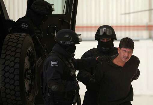 "Federal Police agents escort Carlos Zepeda, alleged member of Zetas drug cartel, right, as he is presented to the media in Mexico City, Tuesday, Jan. 18, 2011. Zepeda and Flavio Mendez Santiago, alias ""El Amarillo,"" alleged member and co-founder of the Zetas drug cartel, were arrested in Villa de Etla, Mexican state of Oaxaca, some 400 km southeast of Mexico City, on Monday. Photo: AP"