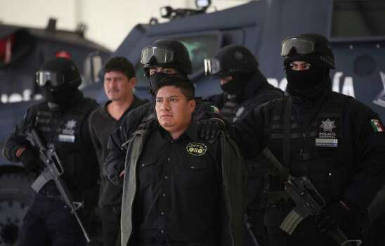 "Federal Police agents escort Flavio Mendez Santiago, center, alias ""El Amarillo,"" alleged member and co-founder of the Zetas drug cartel, during a presentation to the media in Mexico City, Tuesday, Jan. 18, 2011. Mendez Santiago was detained in Villa de Etla, Mexican state of Oaxaca, some 400 km southeast of Mexico City, on Monday. Photo: AP"