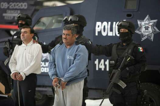 "Eduardo Ramirez Valencia, alias ''El Profe,'' center, and Ruben Barragan Monterrubi, alias ""El Montes,"" are presented to the press at federal police headquarters in Mexico City, Thursday Dec 2, 2010. Alleged members of the Zetas gang, the two are accused of drug trafficking from Panama and Dominican Republic to the United States.  Ramirez is believed to have collaborated closely with the elusive Heriberto Lazcano Lazcano, the alleged leader of the Zetas. Photo: MIguel Tovar, AP / AP"
