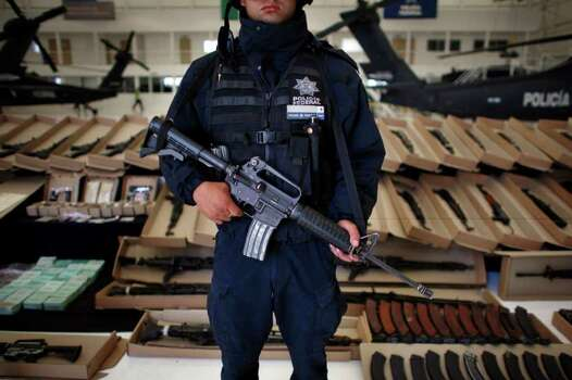 A federal police officer stands guard as seized weapons are shown to the press in Mexico City, Friday, Oct. 22, 2010. An arsenal allegedly seized from Los Zetas drug cartel of high-power rifles, grenades and ammunition were found hidden in a horse trailer, according to police. Two people were arrested in connection with the seizure. (AP Photo/Miguel Tovar) Photo: Miguel Tovar, ASSOCIATED PRESS / AP
