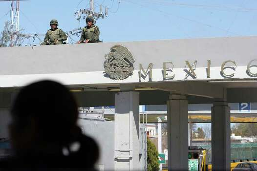 METRO -- Mexican Army personnel guard the port of entry at Ciudad Miguel Aleman, Mexico, Saturday, Feb. 27, 2010. The town, across the Rio Grande from Roma, Texas, and others border cities saw an increased of violence earlier in the week in a turf battle between rival drug gangs, the Zetas and the Gulf Cartel.  JERRY LARA/glara@express-news.net Photo: JERRY LARA, San Antonio Express-News / glara@express-news.net