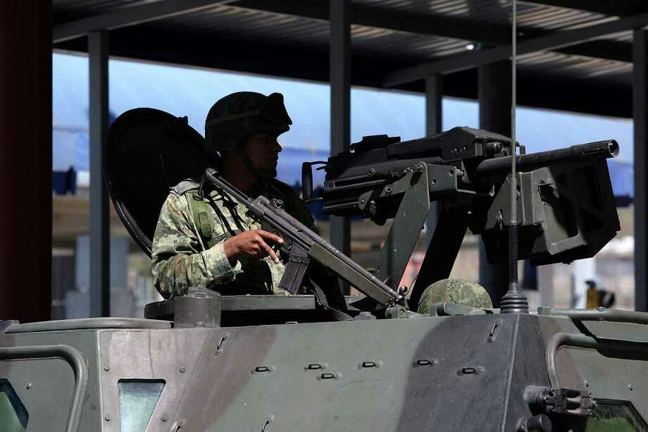 FILE - Mexican Army personnel guard the port of entry at Ciudad Miguel Aleman, Mexico, Saturday, Feb. 27, 2010.   Mexican authorities said Thursday that 21 bodies, some burned, have been found in the border city. Photo: JERRY LARA, San Antonio Express-News / glara@express-news.net