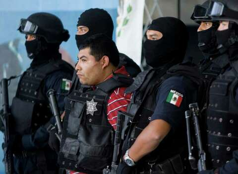 Masked Mexican federal agents escort Jaime Gonzalez Duran,  known as 'The hummer' as he is shown to the media in Mexico City, Friday, Nov. 7, 2008. Gonzalez Duran is allegedly one of the founding members of the Zetas, a group of army deserters who went to work as hitmen for the Gulf drug cartel. Federal Police Commissioner Rodrigo Esparza said Gonzalez Duran deserted from the army in 1999 and was a top lieutenant to current Zeta leader Heriberto Lazcano. Photo: Eduardo Verdugo, AP / AP