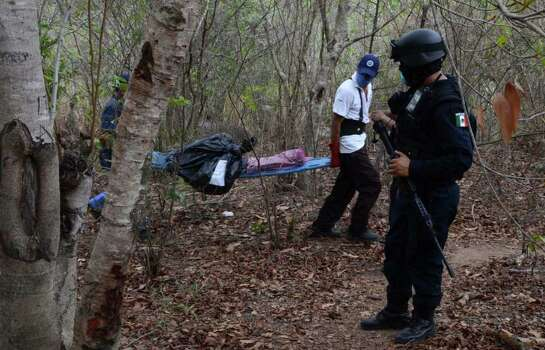 A federal policeman watches as workers remove a body at a site where a mass grave was found in the Pacific resort city of Acapulco, Mexico Thursday June 9, 2011. Officials say they have unearthed at least 10 bodies, two women and eight men,  in a mass grave. Acapulco has become the scene of bloody cartel turf battles. Photo: AP