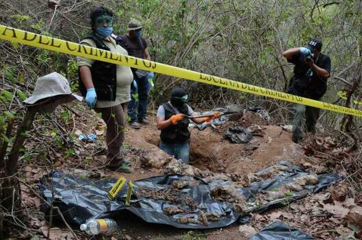 Forensic workers pauses dig up bodies at a site where a mass grave was found in the Pacific resort city of Acapulco, Mexico, Thursday June 9, 2011. Officials say they have unearthed at least 10 bodies, two women and eight men,  in a mass grave. Acapulco has become the scene of bloody cartel turf battles. Photo: AP
