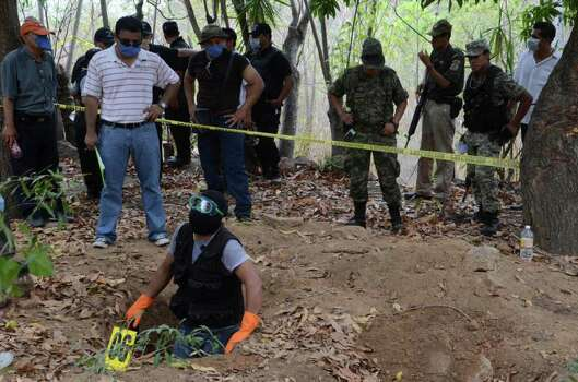 Police and army watch as a forensic worker pauses while digging at a site where mass graves were found in the Pacific resort city of Acapulco, Mexico Thursday June 9, 2011. Officials say they have unearthed at least 10 bodies, two women and eight men, in a mass grave. Acapulco has become the scene of bloody cartel turf battles. Photo: AP