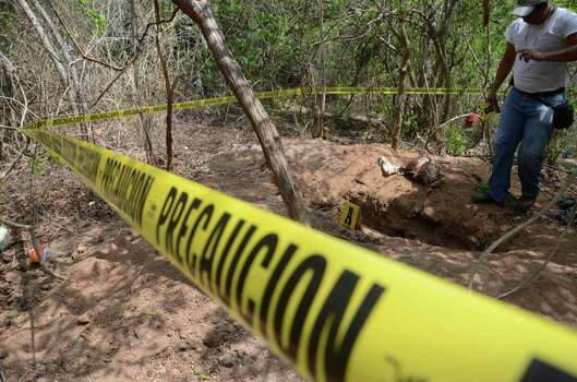 A forensic expert works at a site where a mass grave was found in the Pacific resort city of Acapulco, Mexico Wednesday June 8, 2011.   Police planned to do more digging at the site Thursday, officials said. Photo: AP