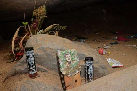 A stone with candles depicting the Santa Muerte and and image of Jesus Malverde, stand at the entrance to a cave near where  graves were found in the Pacific resort city of Acapulco, Mexico Wednesday June 8, 2011. Police and soldiers will continue searching for bodies on Thursday. Photo: AP