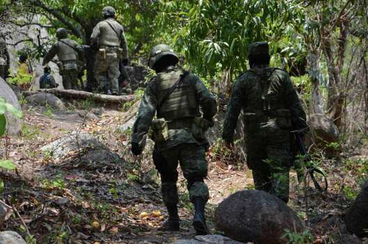 Mexican army soldiers walk up a hill after attending reports of  mass graves found in the Pacific resort city of Acapulco, Mexico Wednesday June 8, 2011. Police and soldiers found ten bodies and will continue digging on Thursday. Photo: AP