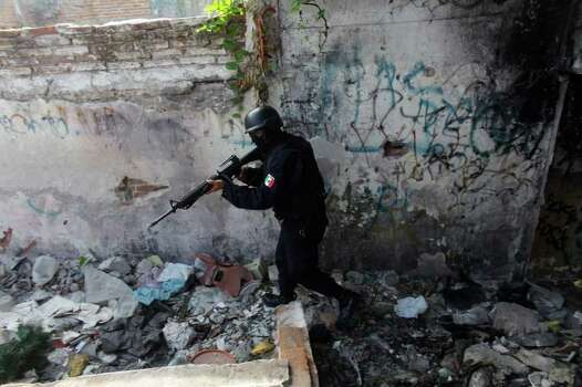 In this Wednesday, April 6, 2011 picture, a state police officer belonging to a newly-formed elite group participates in a patrol during a preventive surprise search at a low-income neighborhood in the Pacific resort city of Mazatlan, Mexico. The so-called Elite Group has been deployed to hotspots around Sinaloa state, dismantling neighborhood gangs in the port city of Mazatlan and making significant arrests, according to local officials. Sinaloa, which shares a name with Mexico's most powerful drug cartel, is known as the cradle of drug trafficking in the country. Photo: AP