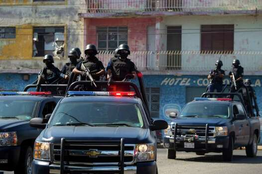 In this Wednesday, April 6, 2011 picture, state police officers belonging to a newly-formed elite group patrol the streets of the Pacific resort city of Mazatlan, Mexico. The so-called Elite Group has been deployed to hotspots around Sinaloa state, dismantling neighborhood gangs in the port city of Mazatlan and making significant arrests, according to local officials. Sinaloa, which shares a name with Mexico's most powerful drug cartel, is known as the cradle of drug trafficking in the country. Photo: AP