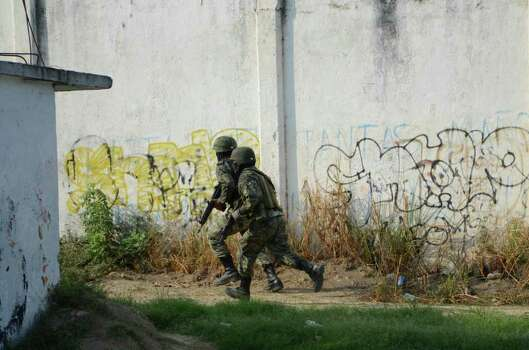 Soldiers give chase after men that were riding in a car that crashed and fell into a ditch, tried to escape while being pursued by federal authorities in Acapulco, Mexico, Monday, May 30, 2011. A decapitated and mutilated body was found in the trunk of the car along with several weapons. Three men were later detained and one escaped according to local media reports. Photo: AP
