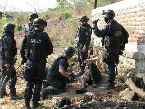 Federal police officers stand over an injured man, allegedly belonging to the La Familia Michoacana drug cartel, after a gun battle was held a day earlier in Jilotlan, Mexico, Saturday, May 28, 2011. According to the Jalisco state coroner's office, 15 alleged members of La Familia Michoacana were killed by federal police, who also arrested 36 gunmen and seized a large cache of weapons. Photo: AP