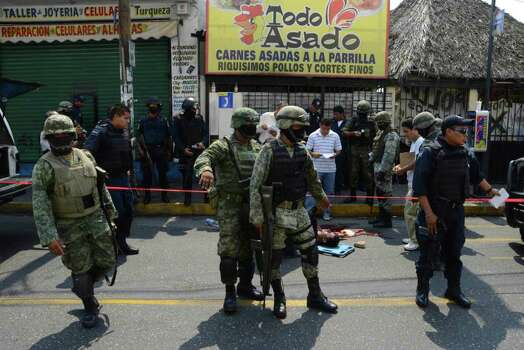 EDS NOTE GRAPHIC CONTENT - Soldiers and federal police stand next to the body of a man that was killed by unknown gunmen near a supermarket in Acapulco, Mexico, Sunday, May 29, 2011. Photo: AP