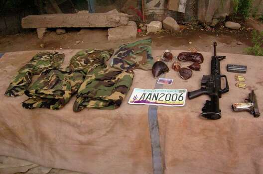 ** RESENDING TO ADD BYLINE **Items that were found after a gunbattle between rival drug gangs are displayed after the army arrival near the town of Ruiz, in the Pacific coast state of Nayarit, Mexico, Thursday, May 26, 2011. The Mexican army said they found  29  bodies wearing fake military uniforms heaped across the roadway and inside bullet-riddled vehicles. Photo: AP