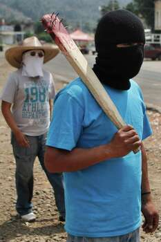 In this photo taken Saturday May 14, 2011, local masked men, one holding a stick with nails on it , stand guard at a barricade in Cheran, Michoacan State, Mexico. The men of Cheran started taking security into their own hands  last month by setting up checkpoints at the entrance of town with tires and sandbags and using guns they stole from local police  after loggers, who residents say are backed by cartel henchmen and local police, killed two residents and wounded several others. Photo: AP